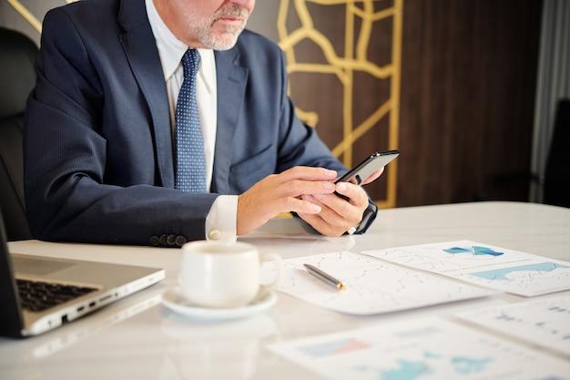 オフィスの机に座って、スマートフォンの画面でテキストメッセージを読んで真面目なシニア起業家