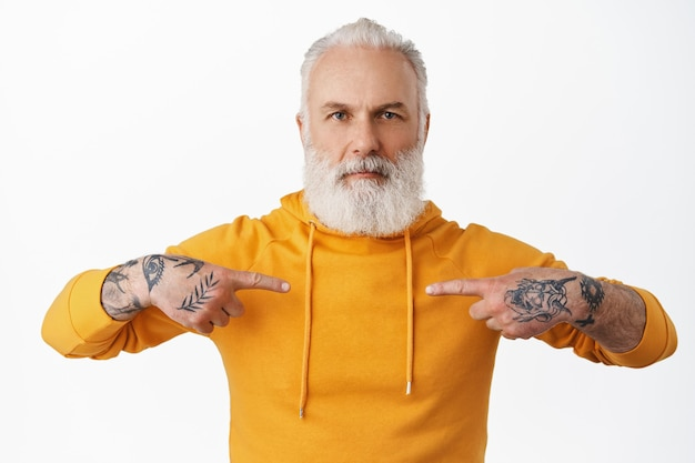Serious senior guy with tattoos and hipster beard, pointing fingers at himself, point at his hoodie, looking at front, standing against white wall.