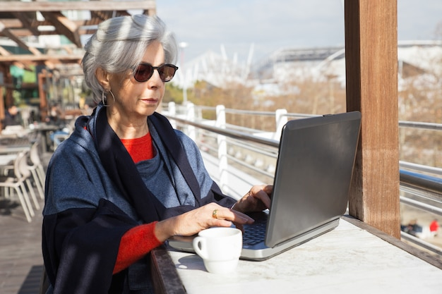Serious senior lady working on computer in outdoor cafe