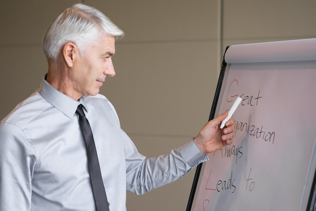 Serious senior lecturer pointing to flipchart
