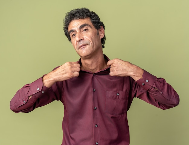 Uomo anziano serio in camicia viola che guarda la telecamera con un'espressione sicura che si aggiusta il colletto