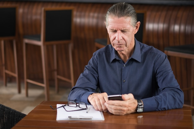 Serious senior man reading message on phone in cafe