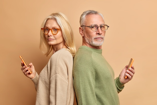 Serious senior woman and her husband hold modern gadgets read media spend free time in internet ignore each other stand backs wear spectacles sweater isolated over beige wall