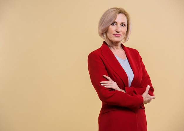 Serious senior woman holding her arms crossed with copy space