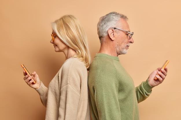 L'uomo e la donna senior seri stanno indietro l'un l'altro usano i telefoni cellulari moderni per la comunicazione online guarda il video online naviga in internet fai acquisti nel webstore isolato sopra il muro marrone