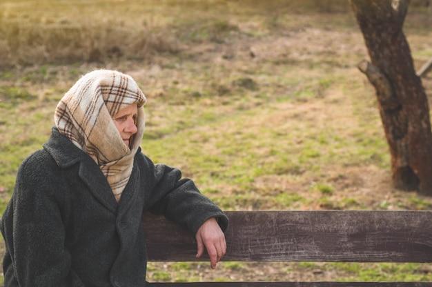 深刻な年配の女性がベンチに座っているとよそ見。杖にもたれて思慮深い古い祖母の肖像画