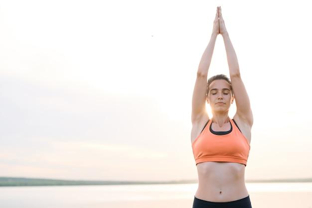夕日の光の中で海に対して立っているとヨガの練習のスポーツウェアで深刻な穏やかな若い女性