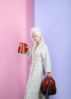 Серьезная сексуальная женщина с пылесосом и чайником занятая женщина с пылесосом и чайником дома