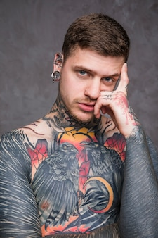 Serious shirtless young man with tattoo on his body looking at camera