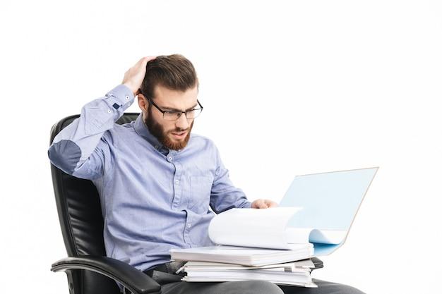 Серьезный шокированный бородатый элегантный мужчина в очках читает документы, сидя в кресле