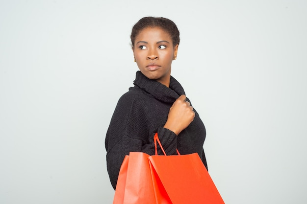 Serious shopper in warm sweater carrying red shopping bags