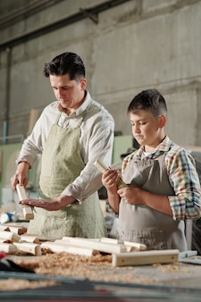 Serious skilled father in apron using sandpaper while polishing wooden planks with son in workshop