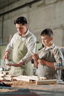 Серьезный опытный отец в фартуке с помощью наждачной бумаги во время полировки деревянных досок с сыном в мастерской