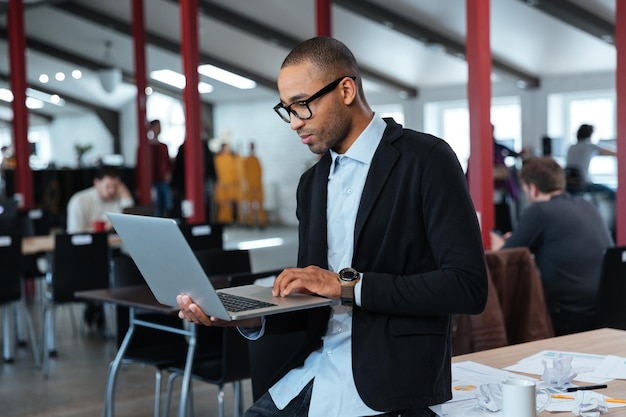 Серьезный умный бизнесмен стоит и использует ноутбук в офисе