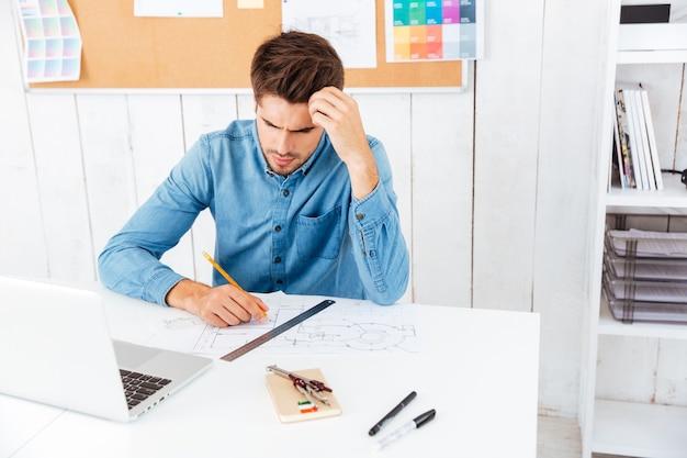 オフィスでラップトップを使用して何かを考えている真面目なスマートビジネスマン