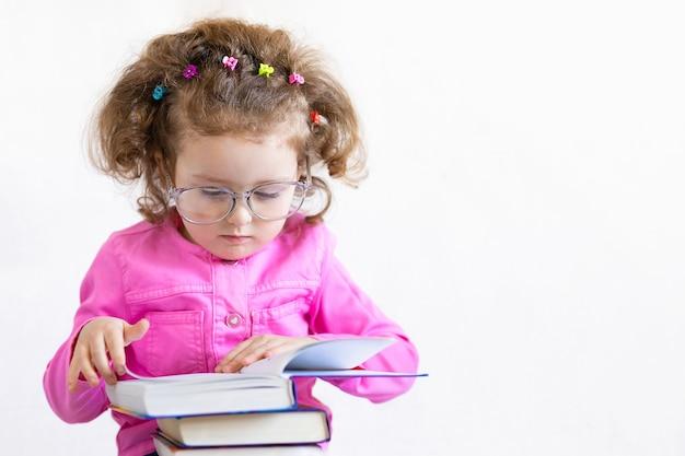 Серьезная умная девушка в больших очках, читая книгу стека. обучение, образование, знания. обратно в школу
