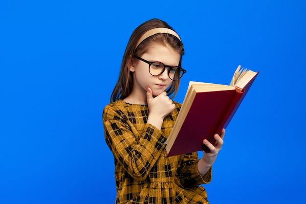 Серьезная умная девушка читает книгу и трогает рукой подбородок в очках