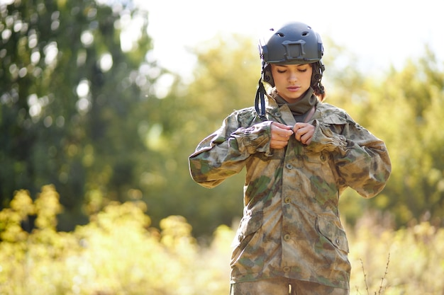 Serious soldier woman wearing jacket in the forest, she is going to hunt