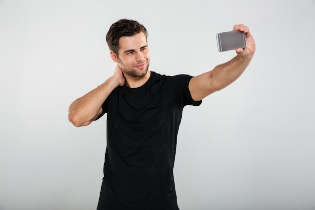 Serious sportsman make selfie by mobile phone