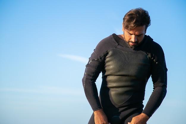 オーシャンビーチでサーフィンのためにウェットスーツを着ている真面目なスポーツマン