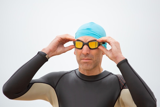 Serious sportsman in wetsuit wearing goggles