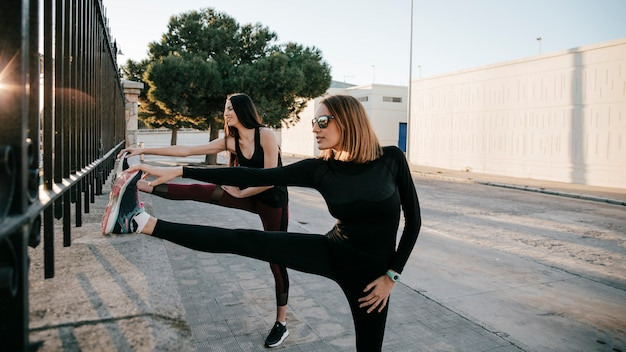 Serious sportswomen stretching muscles on street