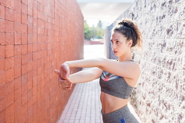 Serious sporty girl stretching arms between walls