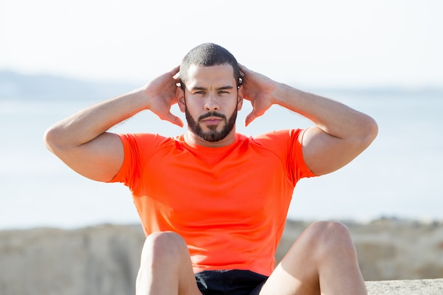 Serious sporty strong man doing sit-ups outdoors