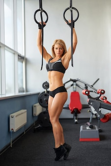 A serious sporty young woman who wears black tight shorts and a tank top is pulling herself up on gymnastic rings. a fitness blond girl is doing back workout in a gym.
