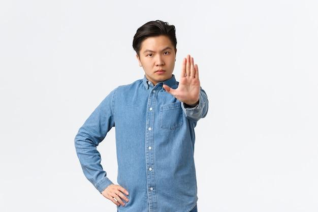真面目で厳格なアジア人男性が手を伸ばして店を止めるジェスチャー、人を叱る、または同意しない、行動を禁止する、悪いことをすることを禁止する、白い背景の上に立って警告を与える。