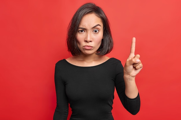 Serious strict asian woman with dark hair raises index finger looks with angry expression warns you about danger wears black clothes isolated over vivid red wall