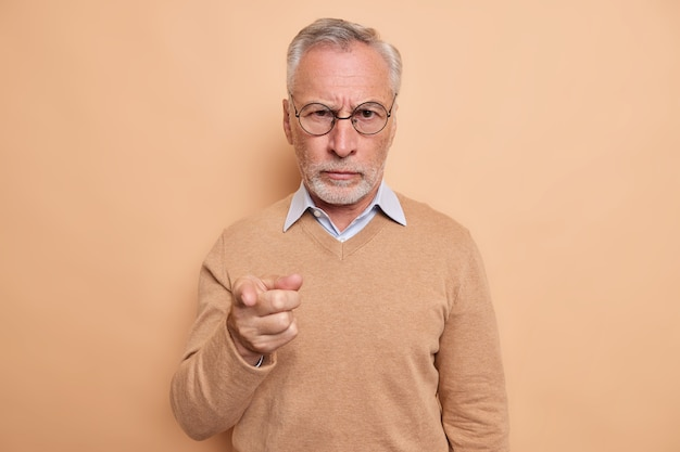 Serious strict bearded elderly man points index finger