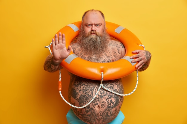 Serious strict bearded man with naked fat body, makes refusal or stop gesture, looks angrily, carries inflated lifebuoy, prevents accident on water, poses