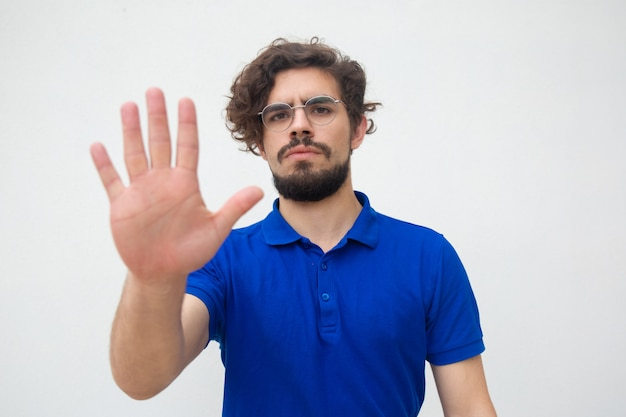 Serious strict guy making hand stop gesture