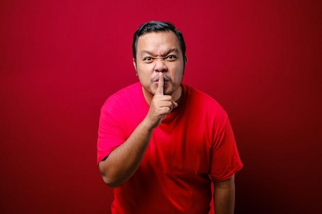 唇の近くで指を持っている真面目な厳格な男は、沈黙を保ち、完全にプライバシーを守るように求めるジェスチャーを示しています。赤い背景で隔離の屋内スタジオショット