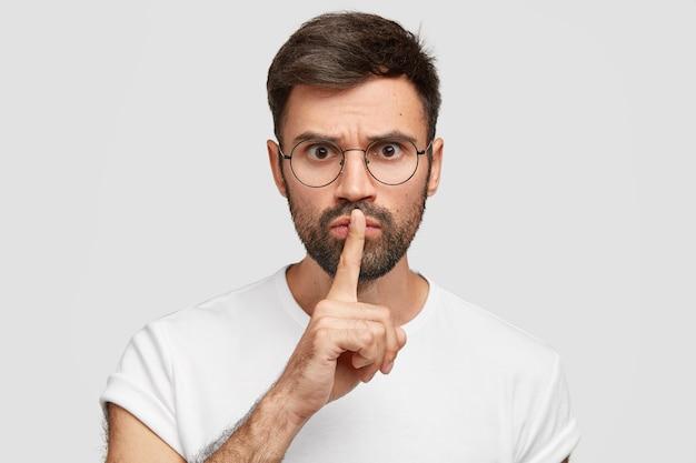 Il giovane insegnante severo e severo chiede di mantenere la voce bassa, mostra il gesto del silenzio