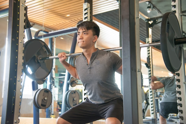 Serious strong asian man standing and lifting barbell in gym