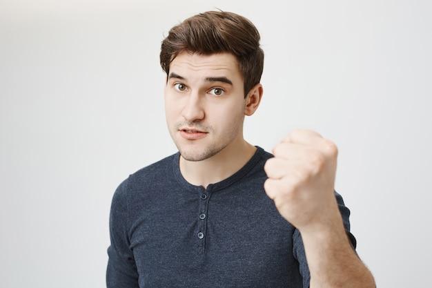 Серьезный сильный мужчина угрожает кому-то кулаком