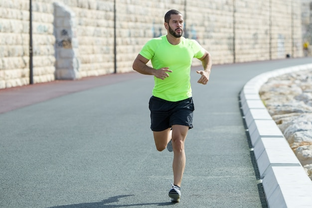 Serious strong sporty man running on road