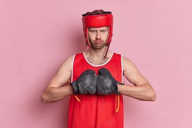 Serious strong unshaven boxer wears hat and boxing gloves keeps hands together prepares for sport competition ready to fight.
