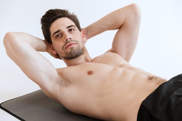 진지하고 강한 젊은 스포츠맨은 복근 운동을 고립시킨다.