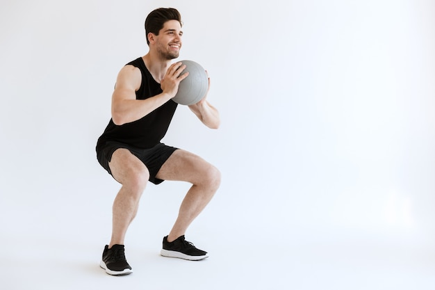 Serious strong young sports man make squats exercise with ball isolated.
