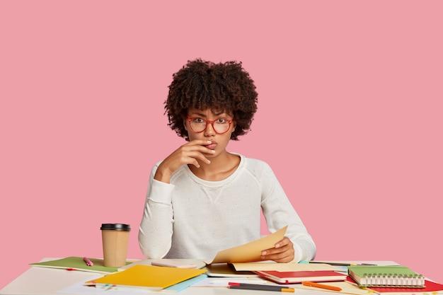 ピンクの壁に向かって机でポーズをとる真面目な学生少女