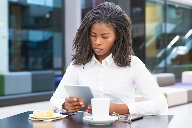 Serious student girl using tablet in cafe