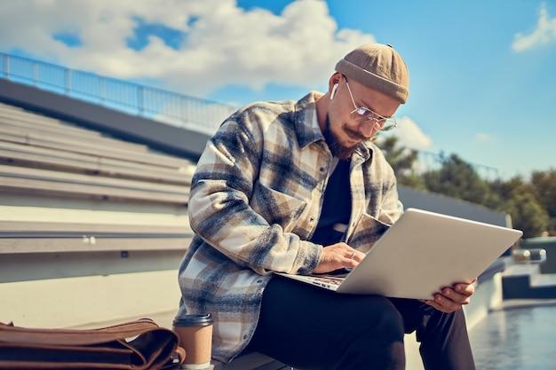 노트북과 헤드폰으로 대학 근처에 앉아 있는 동안 안경 연구를 하는 진지한 학생