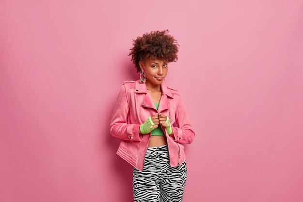 진지한 세련된 아프리카 계 미국인 여성은 세련된 핑크색 재킷, 스포츠 장갑 및 레깅스를 착용하고 자신감을 보이고 곱슬 헤어 스타일을 가지고 있습니다.