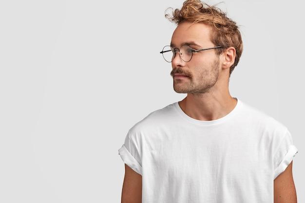 진지한 세련된 힙 스터는 자신감있는 표정으로 옆으로 쳐다보고, 고개를 옆으로 돌리고, 무언가를 멀리 바라보고, 둥근 안경을 착용합니다.