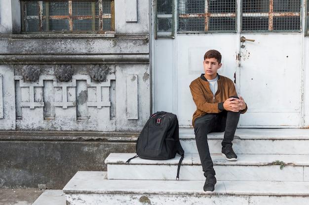 Serious stylish teenage boy sitting on staircase