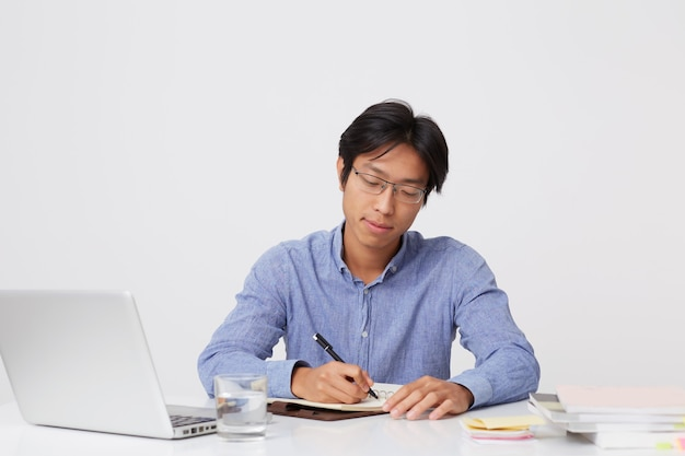 ラップトップで作業し、白い壁の上のテーブルでノートに書くメガネで真剣に成功したアジアの若いビジネスマン
