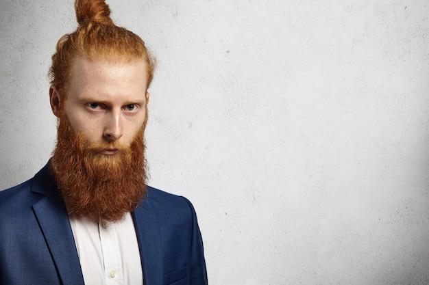 Серьезный успешный рыжий кавказский предприниматель с прической в виде пучка и пушистой бородой одет в стильный синий костюм.